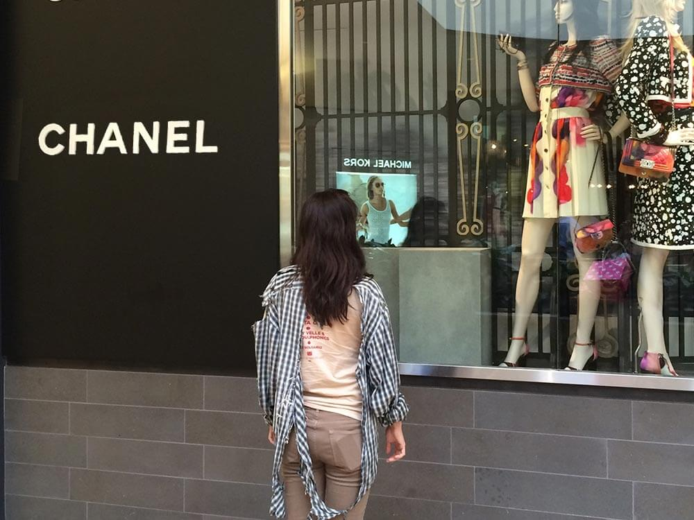 Teresita stands in front of a Chanel store wearing a torn, sun-damaged shirt.